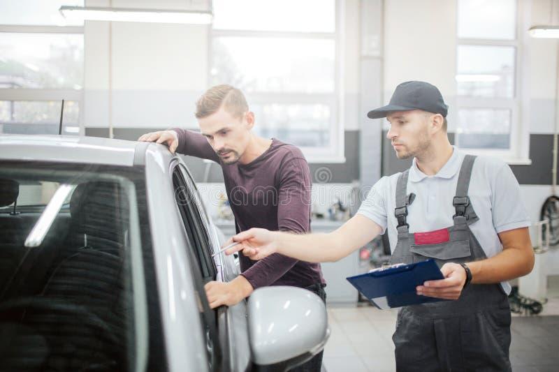 Två allvarliga unga män står på bilen Ägaren lutar till det och ser inom av salong Arbetarpunkter med pennan Han är royaltyfri fotografi