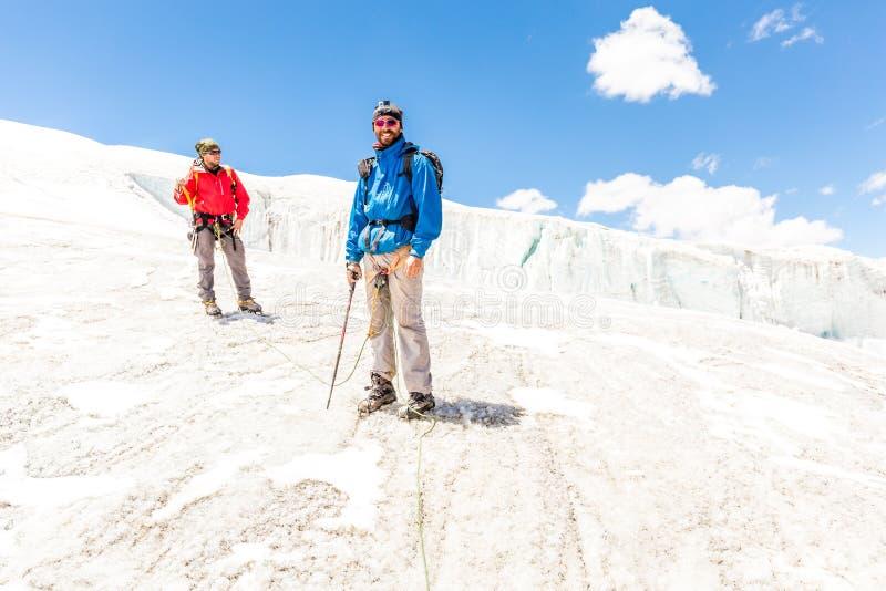 Två alpinistvänner som går berget Anderna Peru för klättringisglaciär royaltyfri fotografi