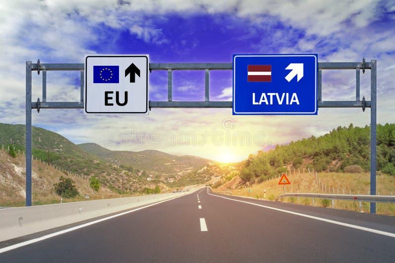 Två alternativ EU och Lettland på vägmärken på huvudvägen royaltyfri fotografi
