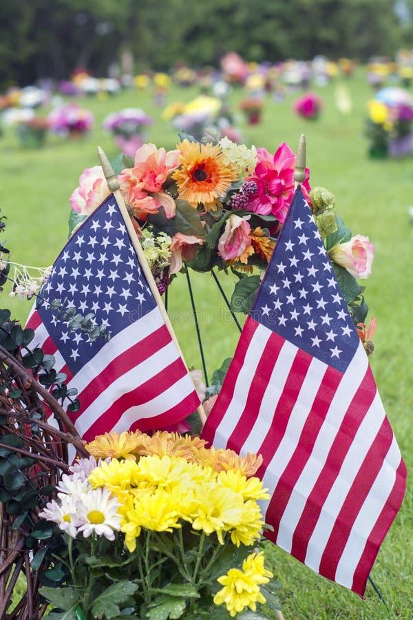 Två amerikanska flaggan och blommor på veteranGraveside fotografering för bildbyråer