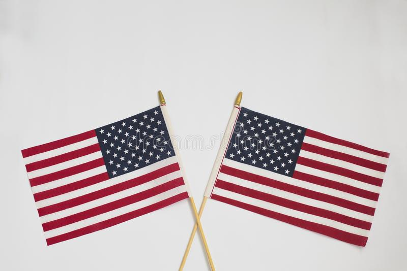 Två amerikanska flaggan som korsar sig på vit bakgrund royaltyfri bild