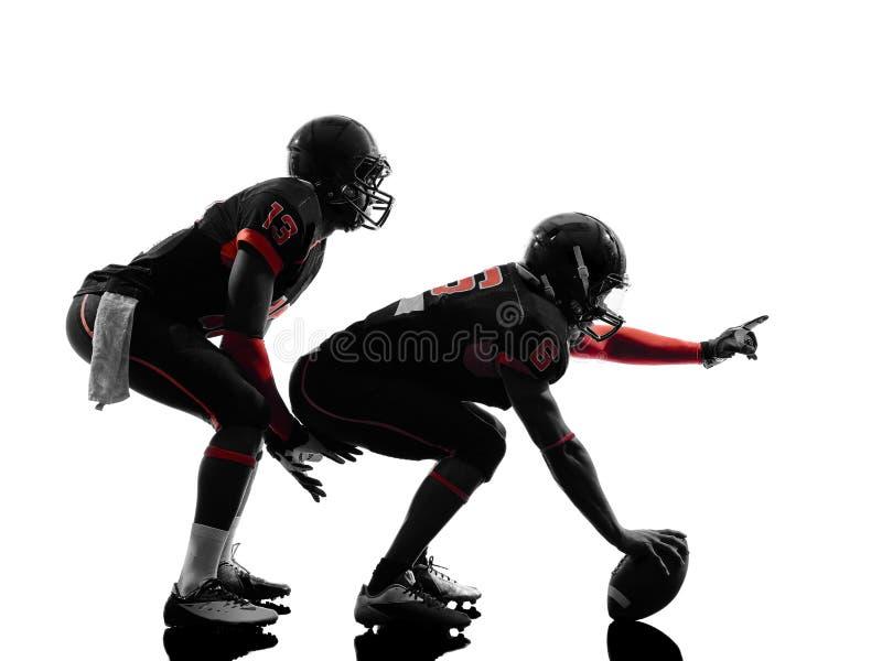 Två amerikanska fotbollsspelare på närkamp om bollenkontur royaltyfri fotografi