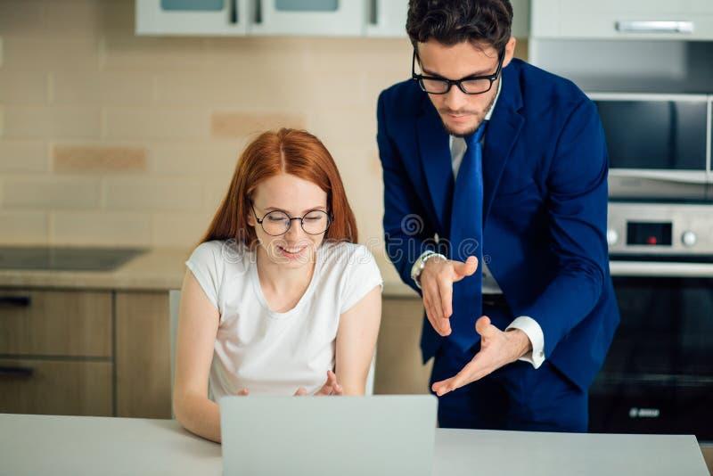 Två analytiker som framme diskuterar online-data av bärbara datorn arkivbilder
