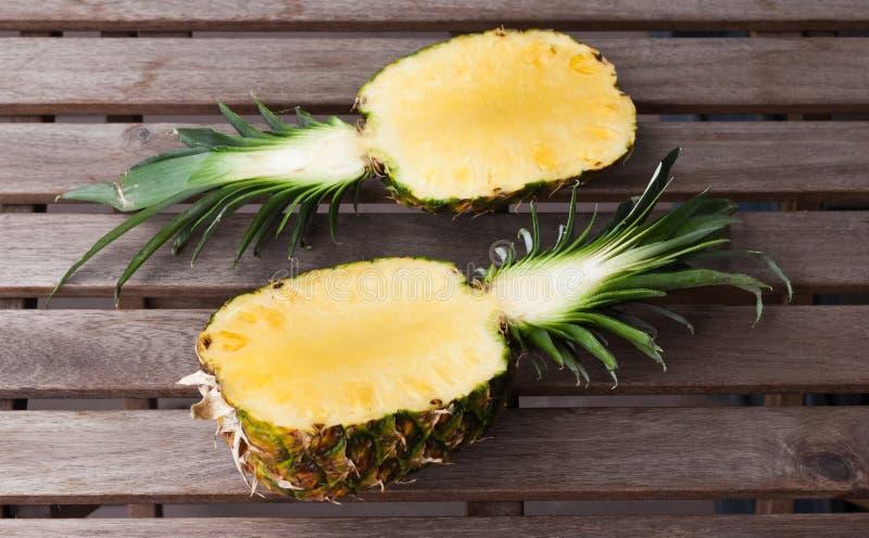 Två ananashalvor på en träbakgrund royaltyfri fotografi