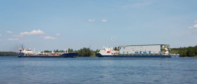 Två annalkande laden skepp på floden royaltyfri foto