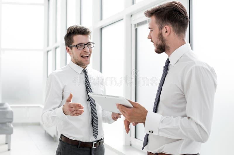 Två anställda med en digital minnestavla som diskuterar något som står i kontoret royaltyfria foton