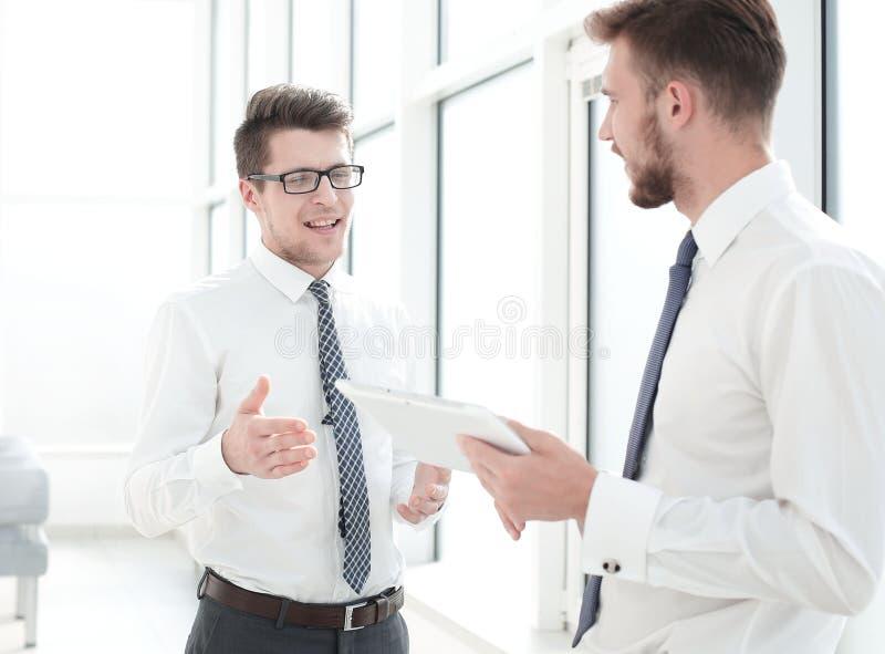 Två anställda med en digital minnestavla som diskuterar något som står i kontoret royaltyfri fotografi