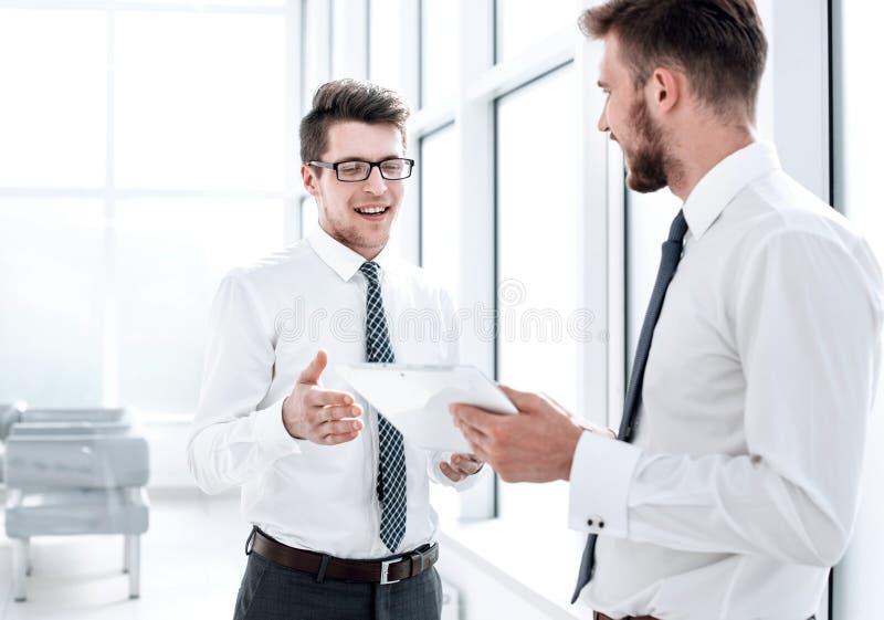 Två anställda med en digital minnestavla som diskuterar något som står i kontoret arkivbild
