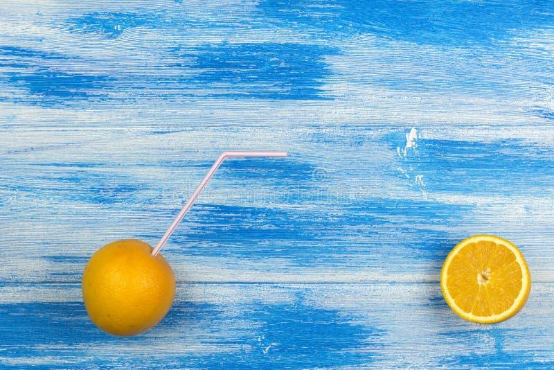 Två apelsiner med ett coctailsugrör Sommardrinkar och sund livsstil Blå bakgrundssommar arkivfoto