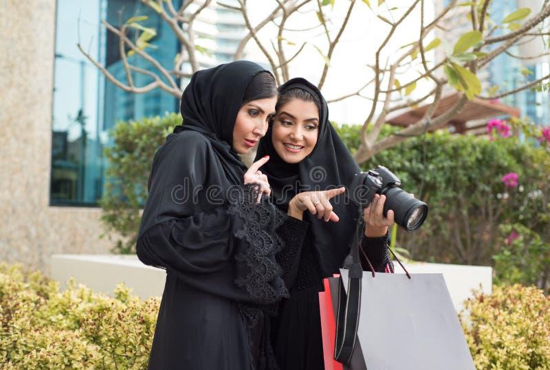 Två arabiska flickor som kontrollerar fotokameran arkivbild
