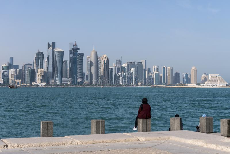Två arabiska mellersta påskkvinnor som sitter på Corniche Broadway och ser på den Doha horisontsikten Qatar Mellanösten arkivbilder