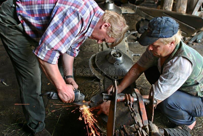 Två arbetare brukar och att bruka utrustningreparation i mekanisk worksho royaltyfria bilder