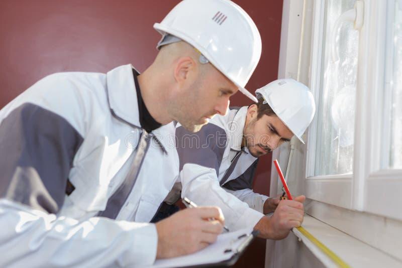 Två arbetare gör mätningsfönster royaltyfria foton