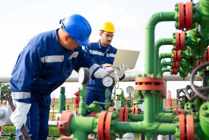 Två arbetare i oljefältet Fossila bränslenbegrepp arkivfoton