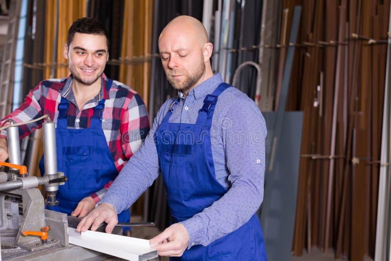 Två arbetare i PVC shoppar royaltyfri foto