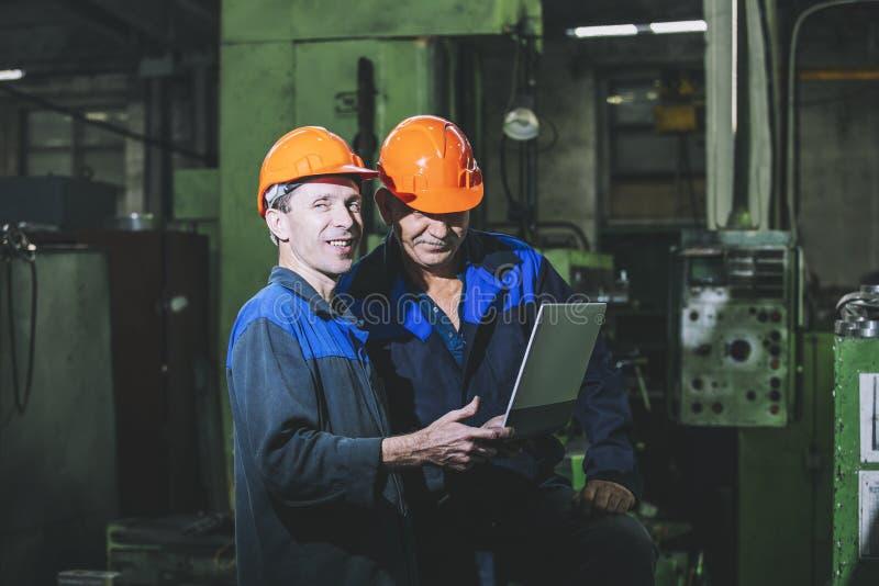 Två arbetare på en produktionsanläggning med en bärbar dator i hand på th arkivbild