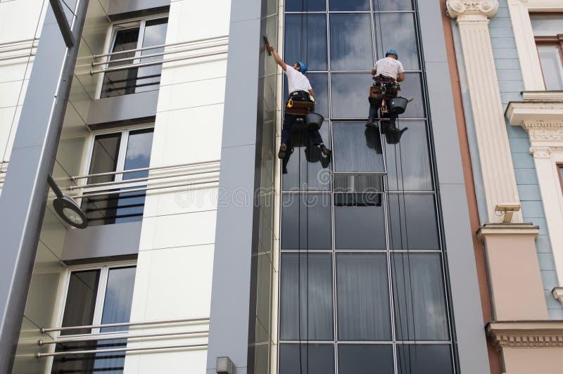 Två arbetare som gör ren fönster på hög löneförhöjningbyggnad arkivfoto