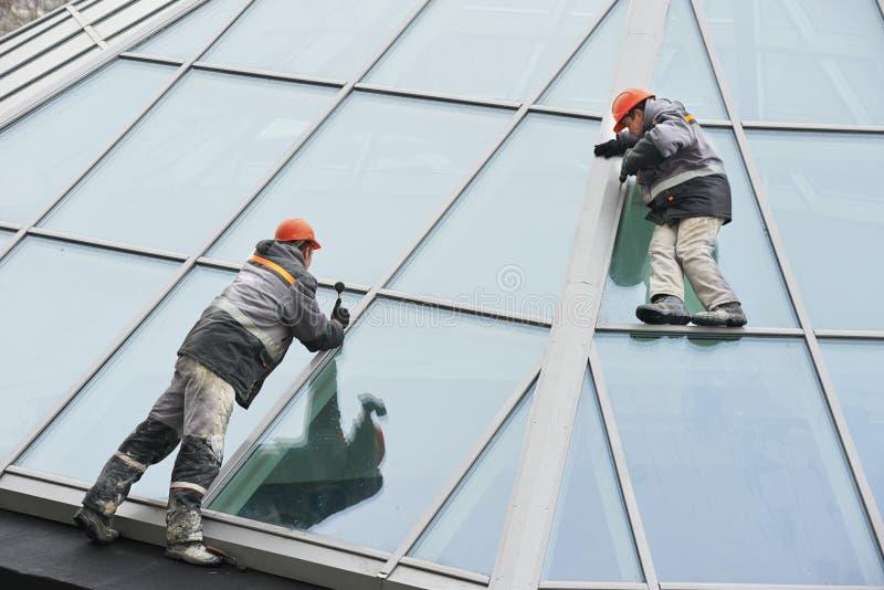 Två arbetare som installerar det utvändiga fönstret royaltyfri fotografi