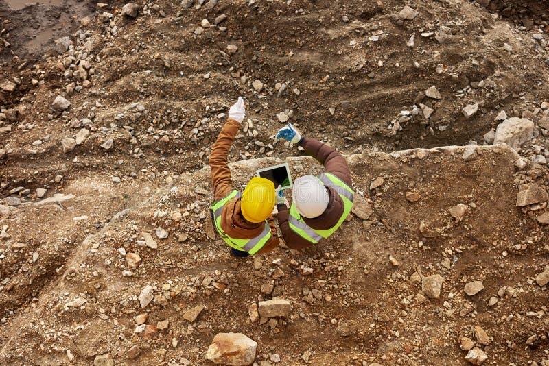 Två arbetare som kontrollerar platsen arkivfoto