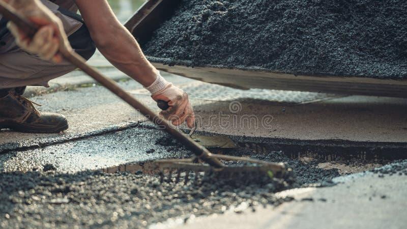 Två arbetare som lägger ny asfalt royaltyfri foto