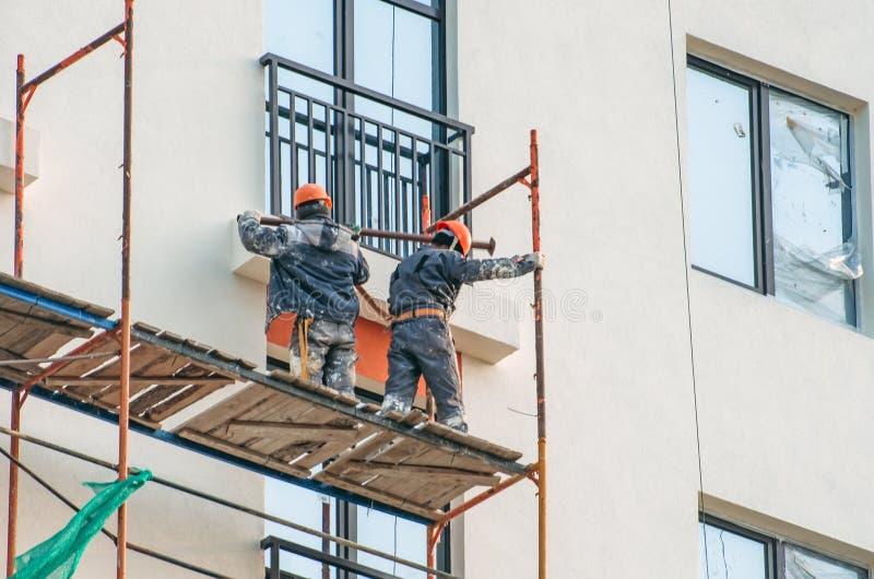 Två arbetare som monterar materialet till byggnadsställning på stadsbyggnad royaltyfri fotografi