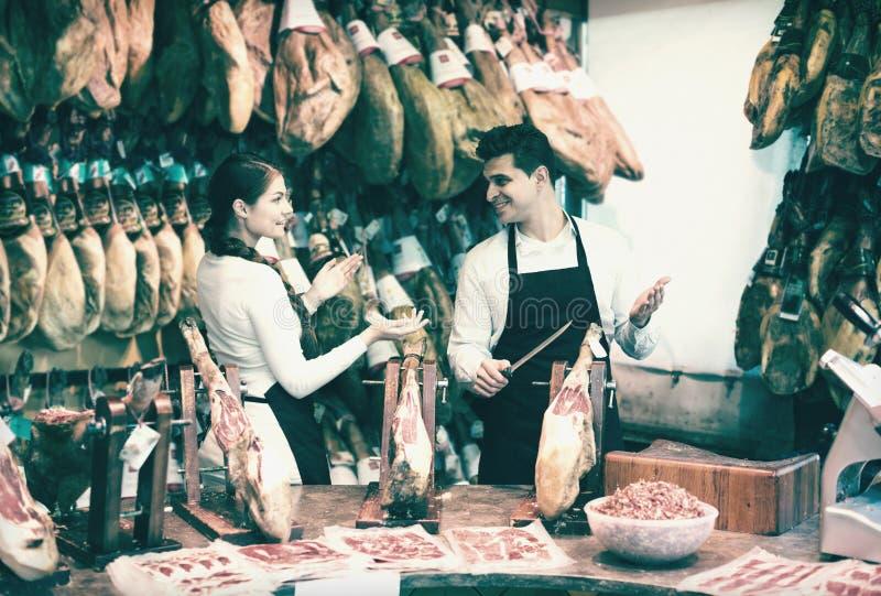 Två arbetare som säljer jamon arkivfoto