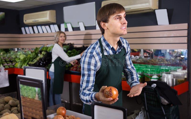 Två arbetare som säljer nya grönsaker fotografering för bildbyråer