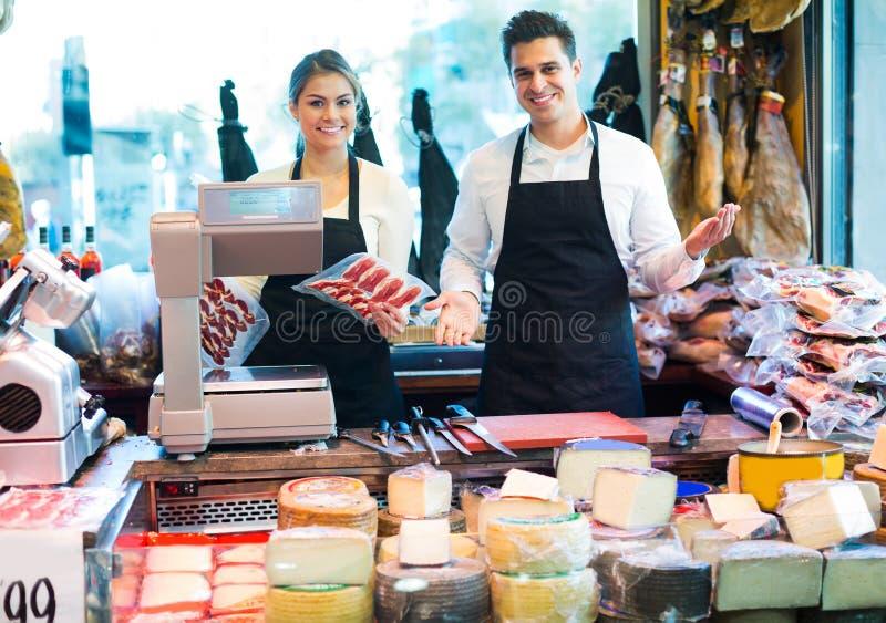 Två arbetare som säljer ost och korvar arkivbild