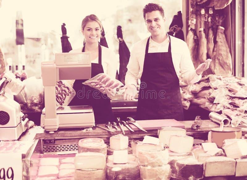 Två arbetare som säljer ost och korvar royaltyfria bilder