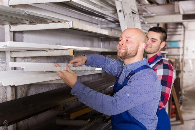 Två arbetare som väljer PVC-fönsterprofil royaltyfri fotografi