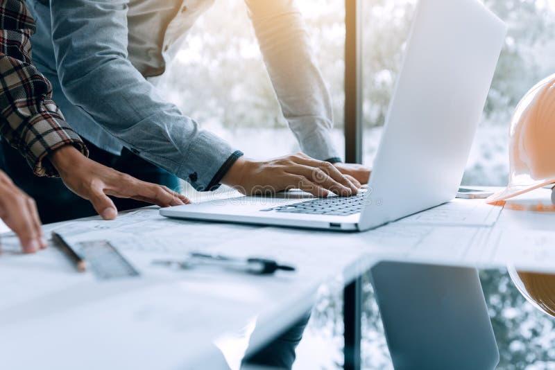 Två arkitektpersoner som arbetar på bärbara datorn och kontrollerar, gör en skiss av I fotografering för bildbyråer