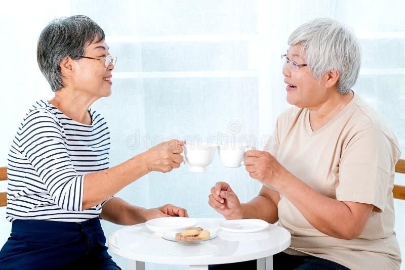 Två asiatiska äldre kvinnor dricker te tillsammans i morgonen och har också några kakor, är de leendet och samtalet om några berä royaltyfri bild