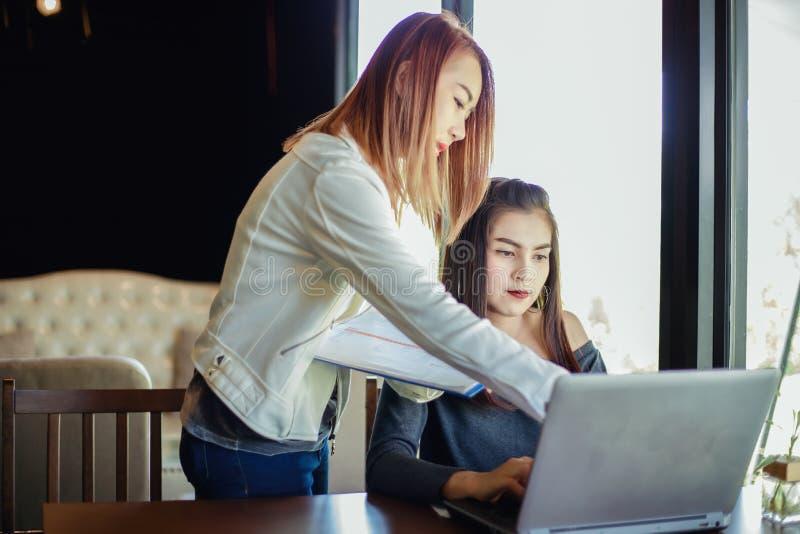 Två asiatiska affärskvinnor som använder anteckningsbokarbete och diskussionsnolla royaltyfria foton