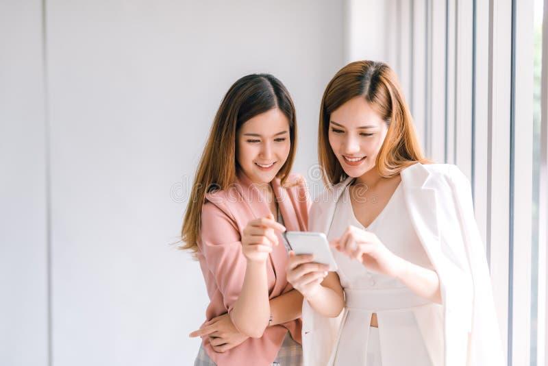 Två asiatiska affärskvinnor som ser smartphoneskärmen genom att använda den smarta telefonen för online-shopping, internet royaltyfri fotografi