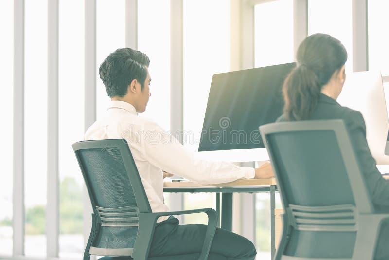 Två asiatiska affärsmän som tillsammans sitter, och arbete i modernt kontor royaltyfri foto