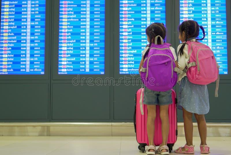 Två asiatiska barnflickor med ryggsäcken som kontrollerar deras flyg på informationsbrädet i terminal för internationell flygplat arkivbild