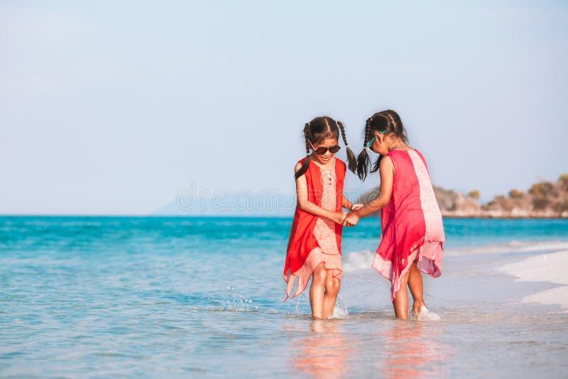Två asiatiska barnflickor som rymmer handen och tillsammans spelar på stranden nära havet i sommarsemester royaltyfri fotografi