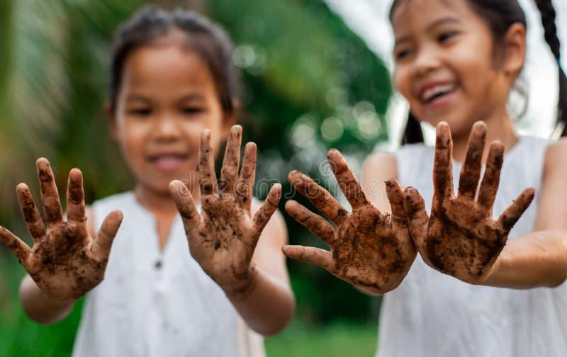 Två asiatiska barnflickor som visar smutsiga händer, når att ha planterat trädet tillsammans i trädgården royaltyfria foton