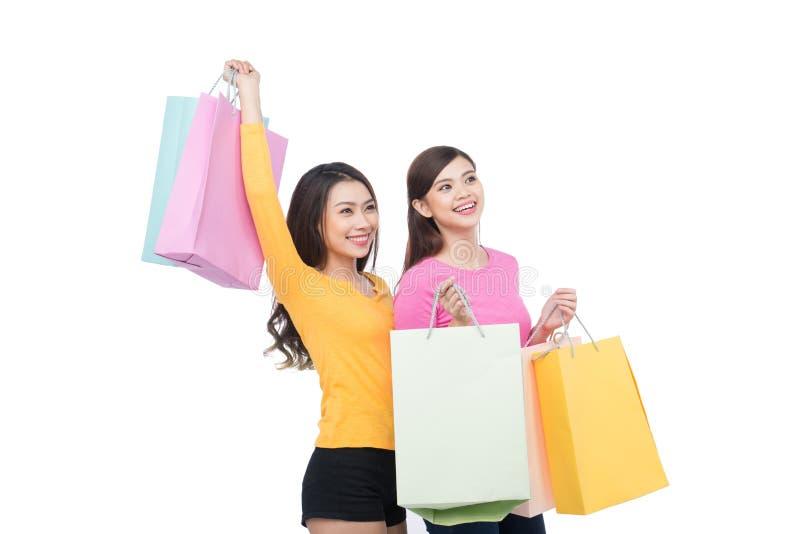 Två asiatiska flickavänner med shopping som isoleras på vit arkivbild