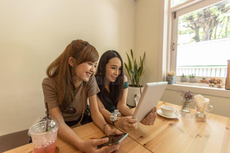 Två asiatiska flickor använder en minnestavla, medan sitta i ett kafé och dricka kaffe royaltyfria foton
