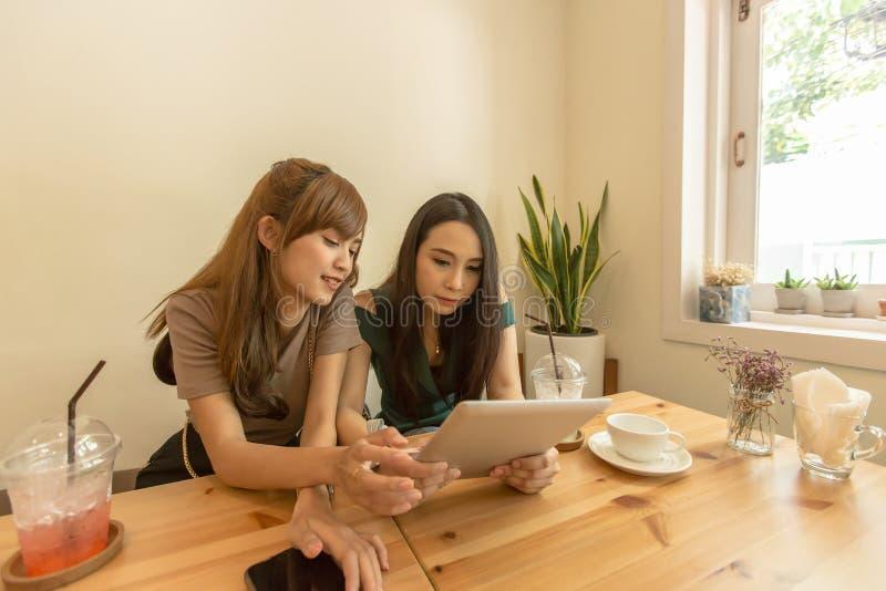 Två asiatiska flickor använder en minnestavla, medan sitta i ett kafé och dricka kaffe royaltyfri foto