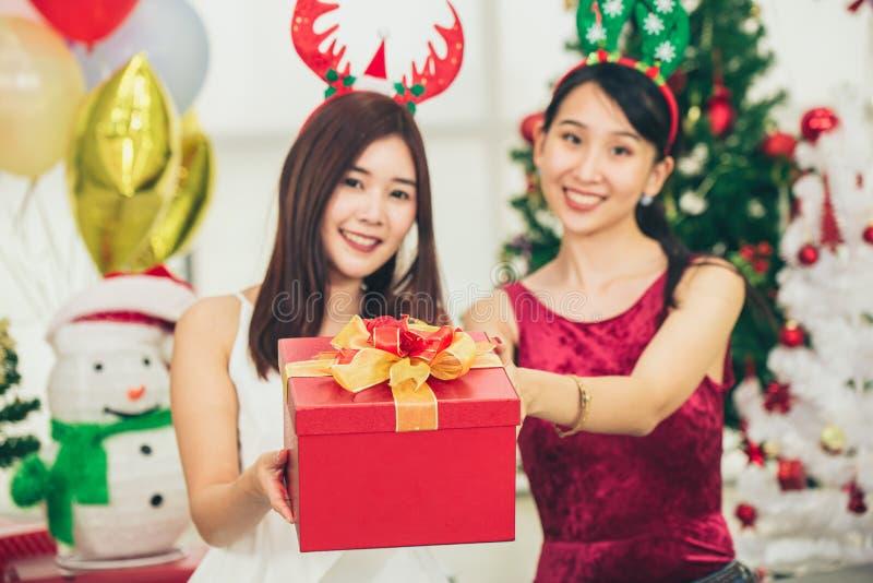 Två asiatiska flickor som är lyckliga jul - nyårsjubileet Eve-festen ger Gift-boxen royaltyfri fotografi