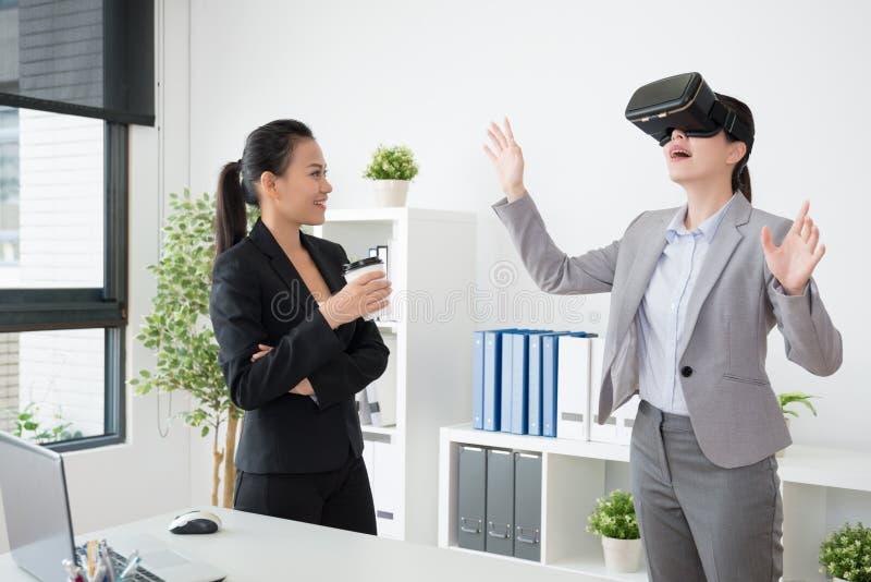 Två asiatiska kollegor erfar 3Den VR fotografering för bildbyråer