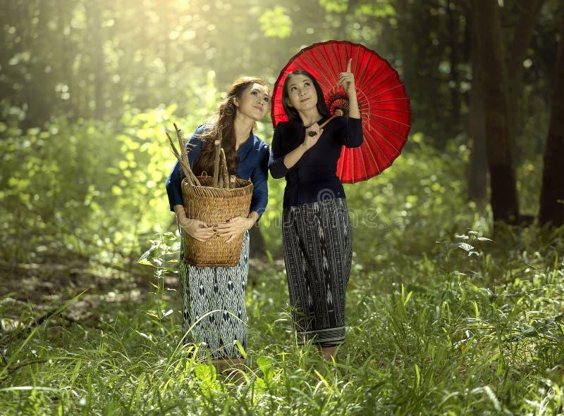Två asiatiska kvinnor i traditionell thai klänning arkivfoton