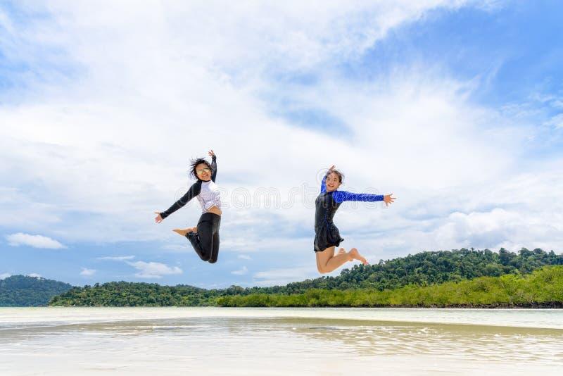 Två asiatiska tonåriga flickavänner som hoppar för att tycka om på stranden arkivbild