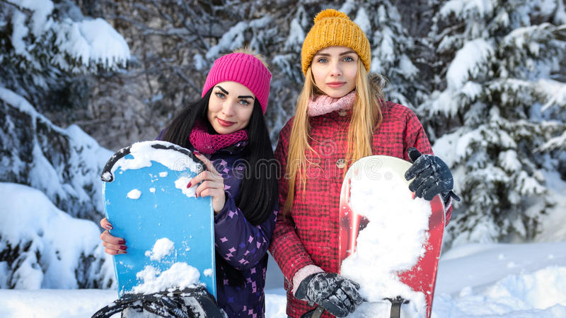 Två attraktiva flickasnowboarders är bland snöig granträd i vinter- och uppehällesnowboardshänderna arkivfoton