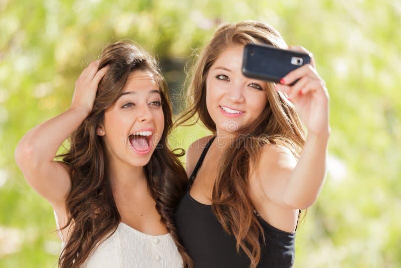 Två attraktiva flickor för blandat lopp som gör Selfies med en Smartphone arkivbilder