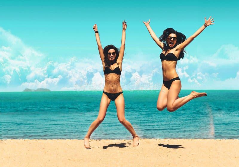 Två attraktiva flickor i bikinier som hoppar på stranden Bästa vän som har gyckel, livsstil för ferie för sommarsemester Lyckligt arkivbild