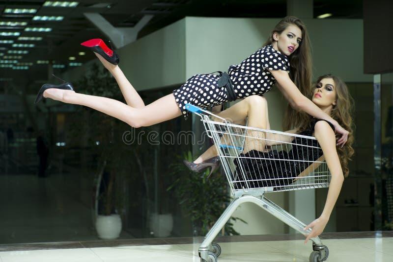 Två attraktiva flickor i shoppingspårvagn royaltyfria foton