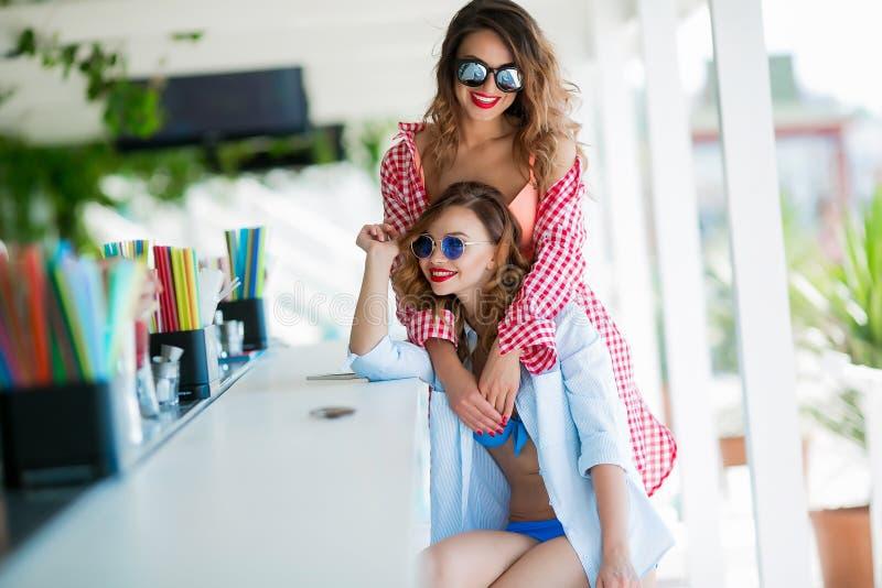 Två attraktiva flickor som vilar på strandstången, dricker en uppfriskande coctail och att skratta och ha gyckel Den ljusa badnin royaltyfri foto